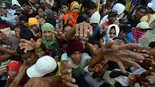 Victims of Typhoon Bopha jostle for position as they beg for relief food being distributed by members of a private ...