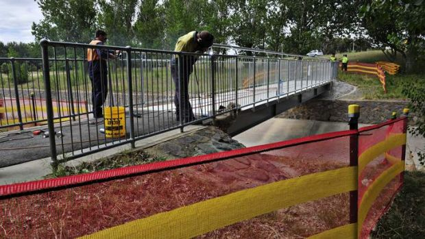 A new footbridge over a stormwater drain in Curtin has the final touches put on it by workers.