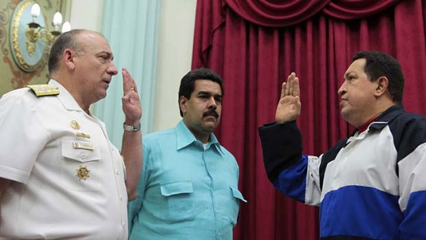 Nicolas Maduro (centre) at a swearing-in with Hugo Chavez (right).