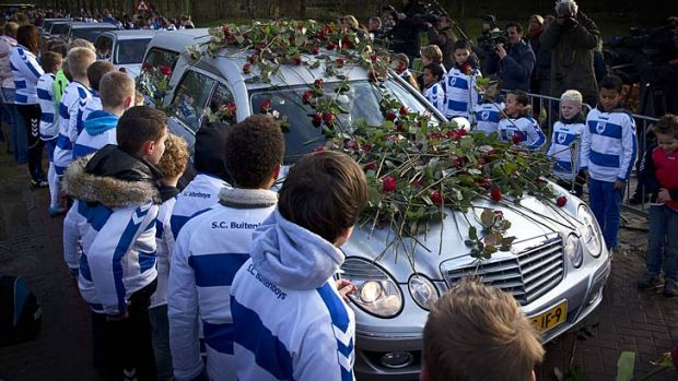 Members of the Dutch soccer club SC Buitenboys place roses on the hearse carrying the body of Richard Nieuwenhuizen.