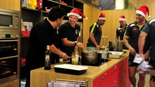 Raiders player Sam Williams is guided by La Scala owner, Gabriele Saccardo, as they prepare meals for families at the ...