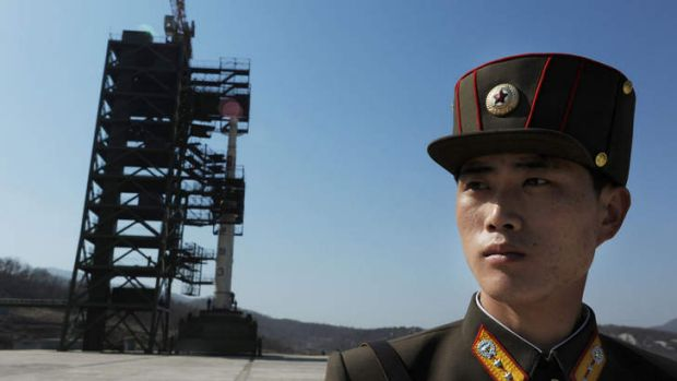 Missile controversy... a North Korean soldier stands guard in front of an Unha-3 rocket at Tangachai -ri space centre ...