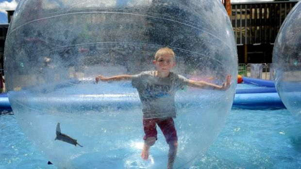 Noah Cross, 6, plays in the floating bubble that has been set up in Civic Square.