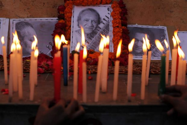 Students and teachers light candles to pay tribute to Ravi Shankar at the Bengali Tola Inter College, where Shankar had ...