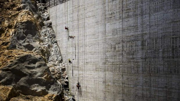 Absailing workers render the surface of the new Cotter Dam wall.