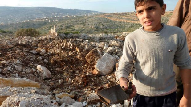 Lopsided conflict ... a Syrian boy next to a crater where a Scud missile landed between Damascus and Homs on Thursday.