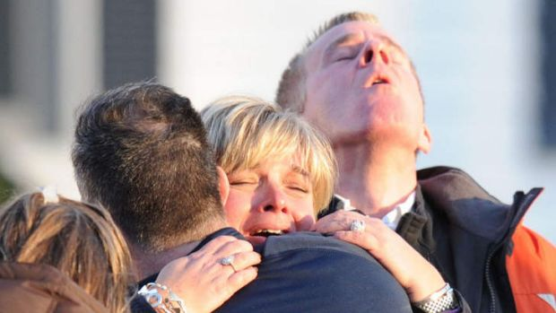 Grief overwhelms a family outside the Sandy Hook elementary school in Newtown, Connecticut.