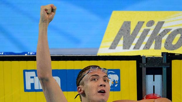 Victory: Robert Hurley raises his fist in triumph after winning the men's 50-metre backstroke final.