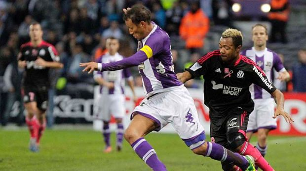 Olympique Marseille's Jordan Ayew (right) chases Jonathan Zebina of Toulouse.