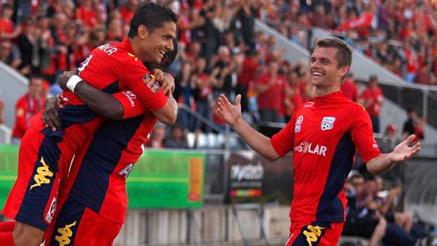 Jubilant: Adelaide's Marcelo Carrusca (left) celebrates his second goal against Wellington with Bruce Djite and Cameron ...