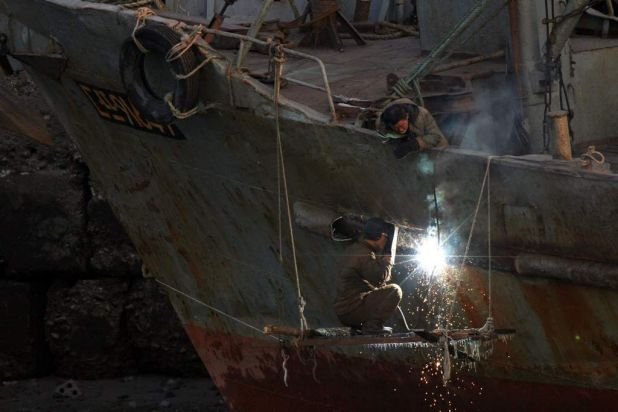 Workers repair a ship on Yalu River in the North Korean town of Sinuiju, opposite the Chinese border city of Dandong.