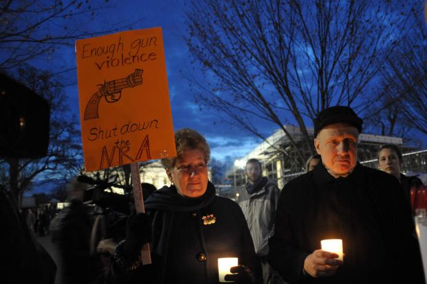 Gun control supporters take part in a candlelight vigil at Lafayette Square across from the White House on in Washington.