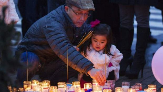 A mourner places joss sticks at a memorial for victims of the recent mass shooting.