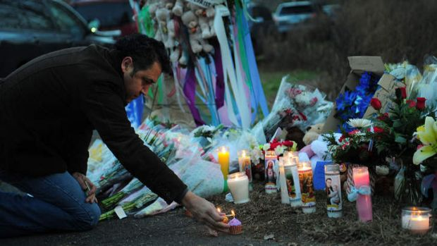 A man pays tribute to the victims of an elementary school shooting in Newtown, Connecticut on Saturday.