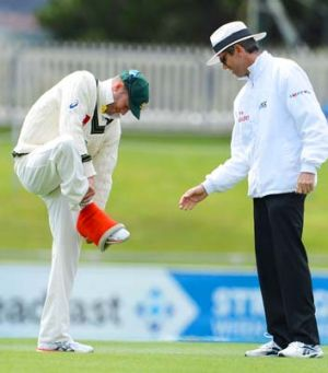 Running repairs: Michael Clarke removes a compression bandage.