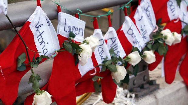 Christmas stockings with the names of shooting victims hang from railing near a makeshift memorial in Sandy Hook.