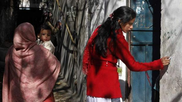 A polio worker marks a house as ''visited'' at a Christian colony slum in Islamabad.
