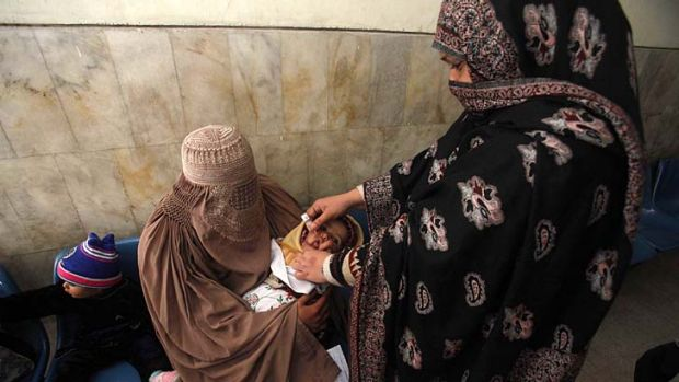 A polio worker gives vaccine drops to a child at a hospital in Peshawar.