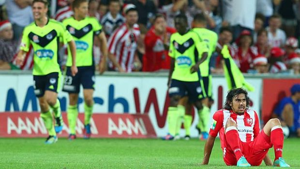 Flattened: Heart's David Williams sits dejected after Archie Thompson's winning goal.