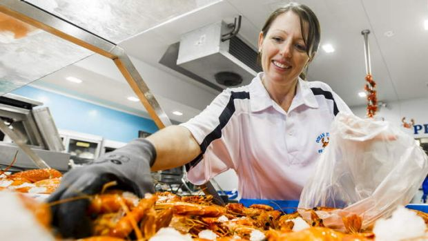 Fyshwick Markets' Ocean Fresh Seafoods' Jenny Jones gathers prawns for a customer.
