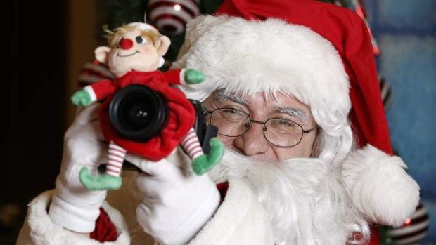 Santa (Rick Goode) tries to get his own photo of the Canberra Times photographer after a long day at David Jones.
