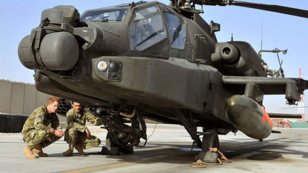 Prince Harry examines the 30mm cannon of an Apache helicopter in Afghanistan, where he is serving over Christmas.