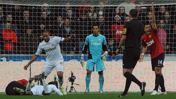 Swansea City's Ashley Williams (6) fouls Manchester United's Robin van Persie (on the ground) during the EPL match on Sunday.