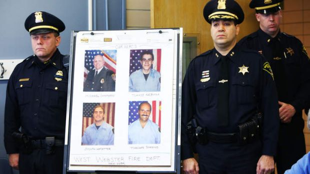 Police stand by the photo of the dead and injured firefighters during a news conference.