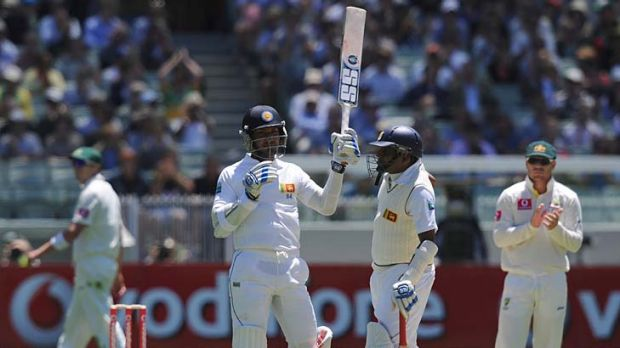 Kumar Sangakkara raises his bat at the MCG on Boxing Day to acknowledge the applause after he became the 11th player to ...