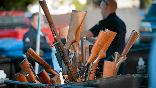 Rifles stick out of a bin during a gun buyback event in Los Angeles on Wednesday.