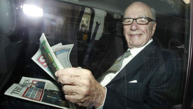 News Corporation CEO Rupert Murdoch holds a copy of The Sun and The Times as he is driven away from his flat in central ...