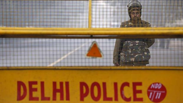An Indian policeman stands guard at a barricade to stop protesters on Saturday after a woman gang raped died in a ...