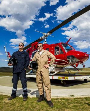 Rural Fire Services' helicopter pilots, Keith Kristian and Bruce Lilburn with one of the helicopters stationed at Hume.