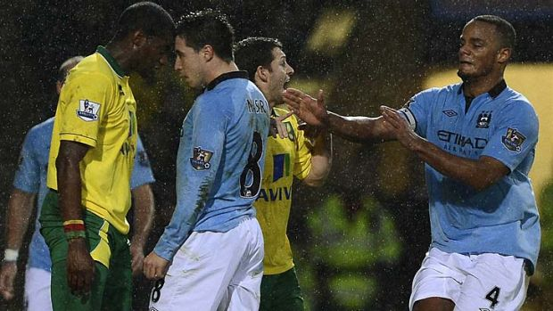 Flashpoint ... Norwich City's Sebastien Bassong (L) clashes with Manchester City's Samir Nasri.