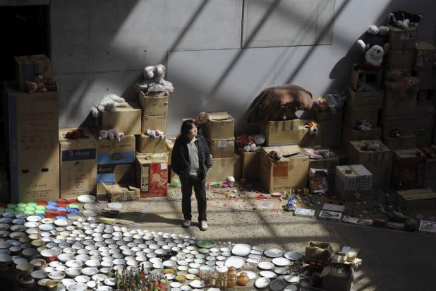 "Artist Song Dong stands amongst his art installation ""Waste Not"" of 10,000 items from his mother's house, which is ..."