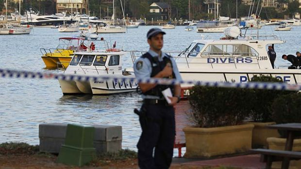''My heart goes out to them'' … police divers remove the body of the woman who went missing off her boat in Rose Bay.