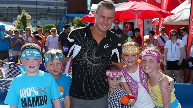 Lleyton Hewitt poses for photographs with children on day two of the Brisbane International.
