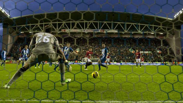 Seven points clear ... Javier Hernandez scores past Wigan's goalkeeper Ali Al-Habsi.