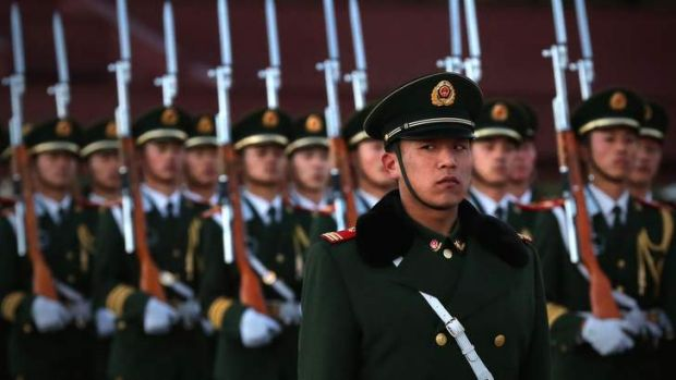 A paramilitary police officer stand guard during the flag-lowering ceremony at Tiananmen Square in Beijing.