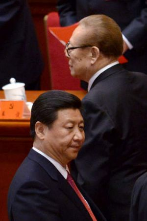 Chinese former president Jiang Zemin walks by Xi Jinping after the closing of the 18th Communist Party Congress at the ...