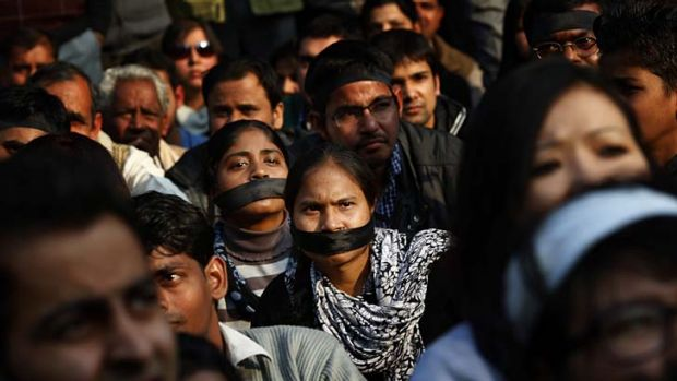 Women wear black bands across their face as they join a gathering mourning the death of a gang rape victim in New Delhi, ...
