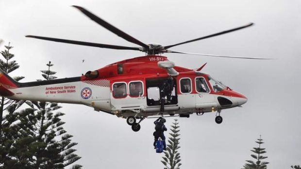 Ambulance Paramedics treat a spear fisherman who got into difficulties in the water  in Storm bay at Kiama on Tuesday, ...