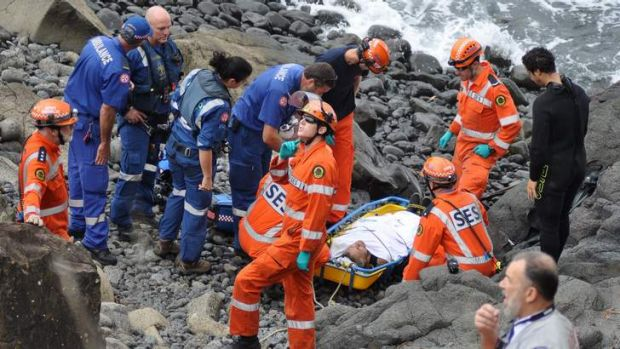 Ambulance Paramedics and SES personel treat and prepare to move a spear fisherman at Storm bay.