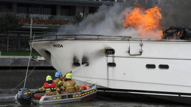 Three men in a tinny: Firefighters extinguish a burning yacht in March last year.