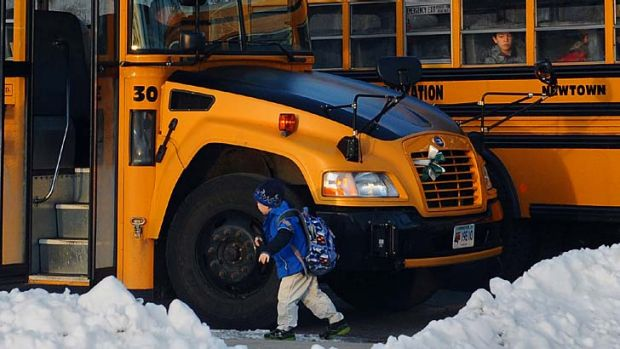 Back to school ... children board a bus on the first day of classes after the holiday break in Newtown.