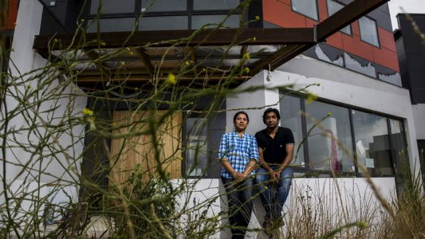 Kazi Nahar and Asik Hossain outside their unfinished  home in Franklin.