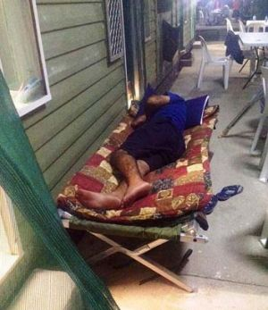 An asylum seeker sleeps outside to escape stifling heat.