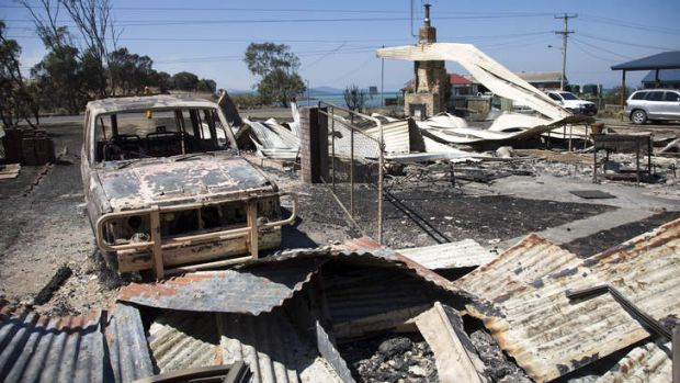 The charred remains of a car and houses at Dunalley on the east coast of Tasmania.