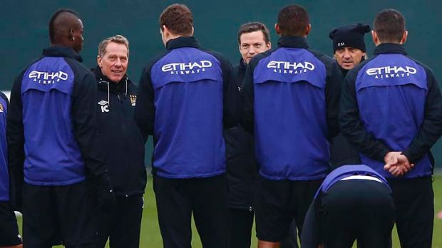 Mario Balotelli (left) listens to manager Roberto Mancini (second right) during a training session at the Carrington ...