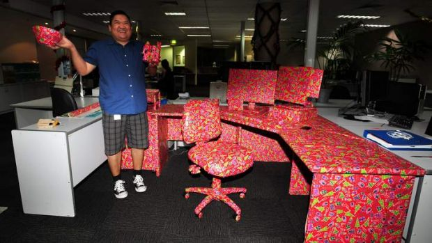 Canberra Times staffer Anderi Abdulhamid unwraps his Christmas prank - his entire workstation.